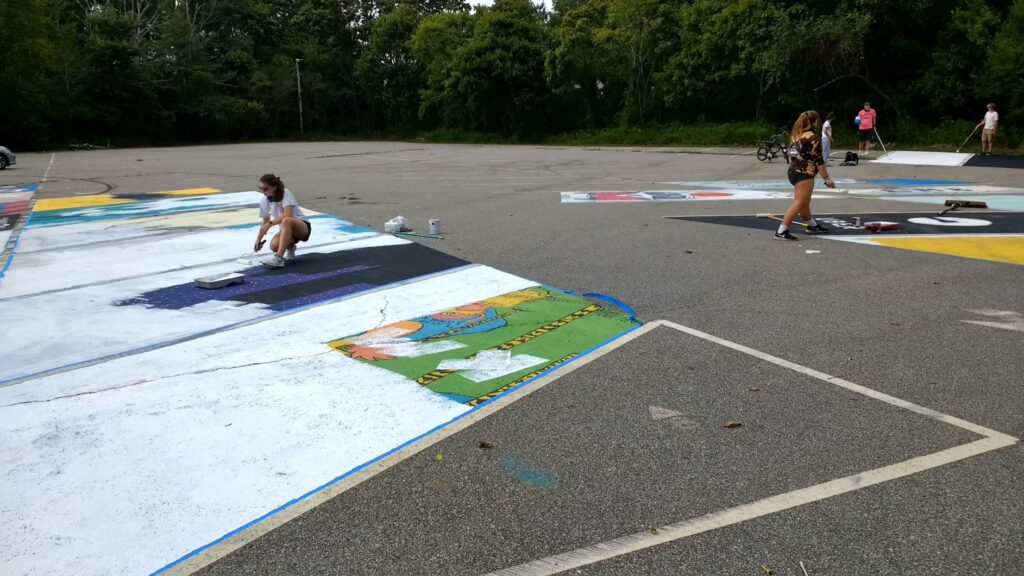 INCOMING SENIORS, including Lauren Martland, at left with roller, paint over the images created a year ago by the Class of 2020, in preparation of adding their own paintings.